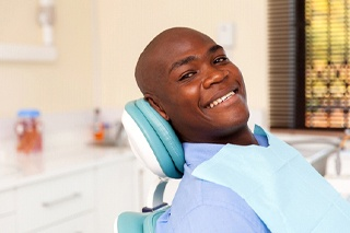 person smiling while sitting in dentist's chair