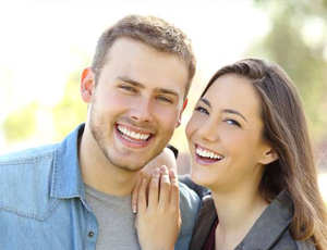 Couple with beautiful teeth after porcelain veneer treatment