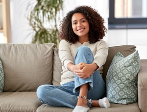 A young woman sitting on a couch and smiling after SureSmile Treatment