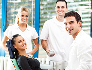 Smiling woman in dental chair with team members