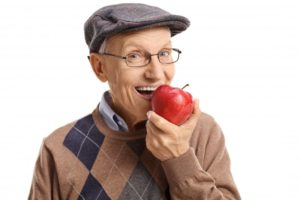 An older man eating an apple.