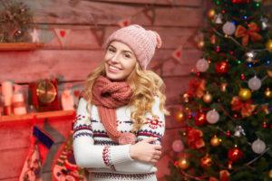 Woman smiling near Christmas tree