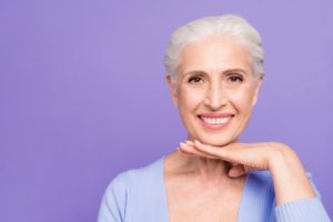 Smiling woman with implant-retained dentures in Plano