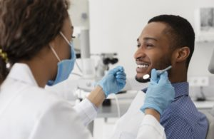 young man smiling at his dentist in Plano