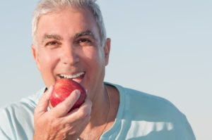 Man with dentures in Plano biting an apple.