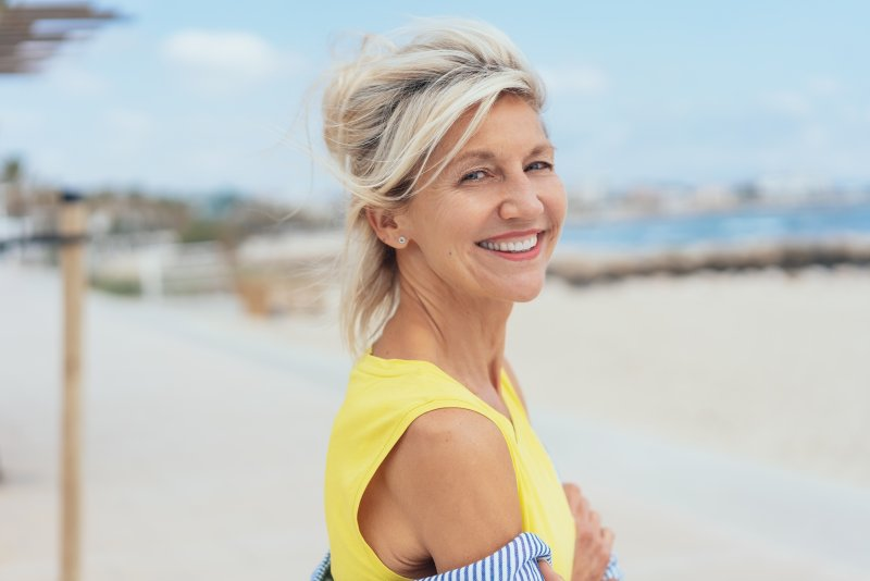 Woman with dental implants smiling by the lake