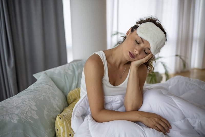 young woman in bed with toothache at night